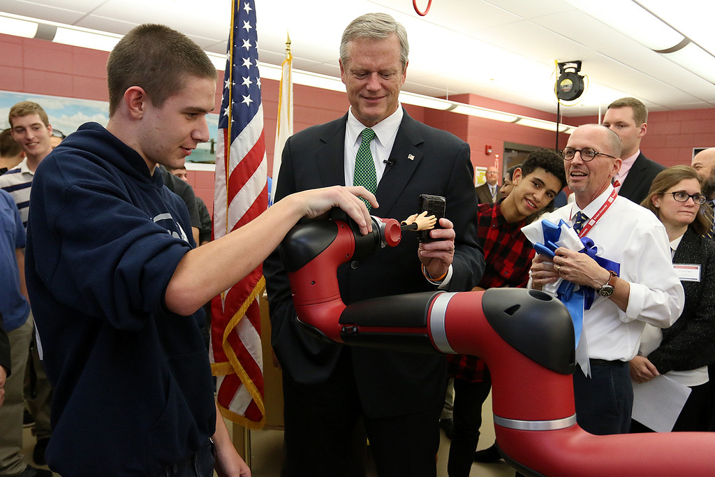 . Gov. Charlie Baker is visiting Nashoba Tech on Wednesday to tour the school\'s Engineering Academy. The Academy received $495,000 in state grant funding last year and has upgraded classroom equipment using that funding. They held a ribbon during his visit for the Engineering Academy. Just after the ribbon cutting senior Drew Norton, 17, from Townsend showed Baker how their robotic arm could grab his wallet. Just behind baker is Jeff Scheminger, in white shirt, the engineering and robotics instructor. SUN/JOHN LOVE