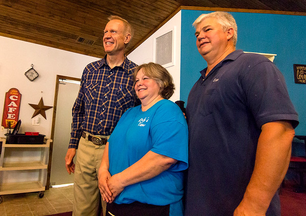 Gov. Bruce Rauner, left, poses for a photo with Karla and Brian Yocum, owners of Karla's Down Home Diner in Greenup Wednesday afternoon.<br /> Keith Stewart Photo
