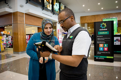 Staff member Kaled Mahamoud helps customer Maysa Khudrut at the first pop up outlet at Point Cook Town Centre, Point Cook.