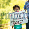 Six-year-old Jayden Robles, cousin of organizer Dawn Hyde, holds up a sign made by his grandma.