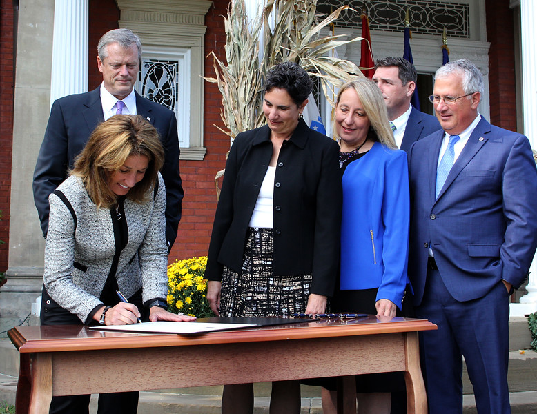 Swampscott, Ma. 9-13-17. Governor Charlie Baker watches as Lieutenant Governor Karyn Poito signs 300th Community Compact at Swampscott Town Hall as Naomi Dreeben, chairman of Swampscott Selectman, State Rep Lori Ehrllich,  Swampscott Town Administrator Sean Fitzgerald, and State Senator Thomas McGee look on.