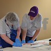 Deanna Thornton, co-founder of The Gracie Center, helps Jimmy Colgan of Genoa package a pizza during a fundraiser on April 30. The Gracie Center provides programming for adults with developmental disabilities.