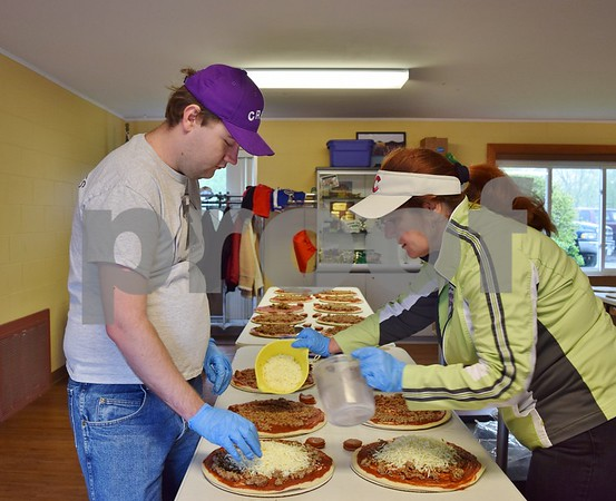 Daniel King, 26, and his mom, Barb King, both of Sycamore, add ingredients to some of the 720 pizzas made during The Gracie Center's fundraiser on April 30. The organization provides programming for adults with developmental disabilities.