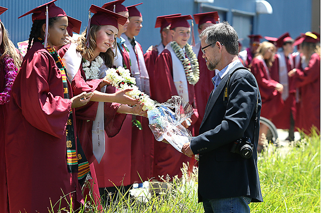 . Don Smith delivers a flower lei to his daughter Matea, waiting with her classmates to march into Kaiser Permanente Arena for Santa Cruz High\'s graduation Friday. (Dan Coyro -- Santa Cruz Sentinel)