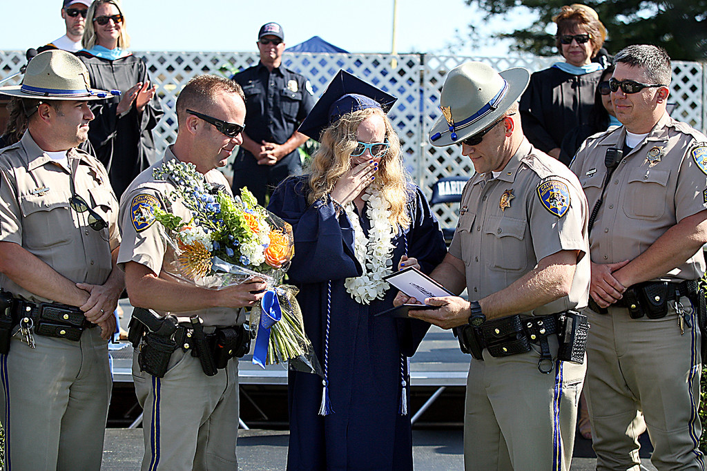 . Sara Jessica Pedro is surprised by more than a dozen California Highway Patrol officers who came forward to present Pedro with her diploma at Aptos High\'s graduation Thursday.  Pedro\'s father--CHP Officer John Pedro--was killed on duty in 2002. (Dan Coyro -- Santa Cruz Sentinel)