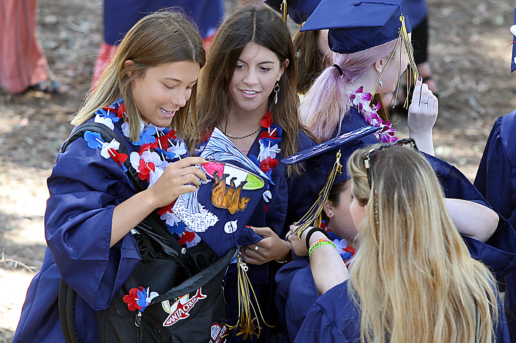 . Soquel High graduating seniors compare decorated mortar boards Friday morning.  (Dan Coyro -- Santa Cruz Sentinel)