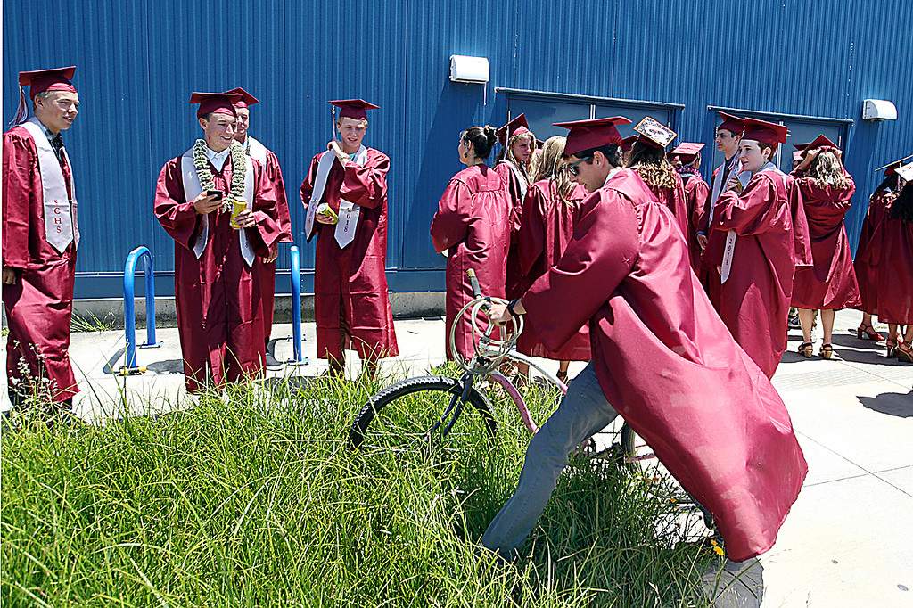 . Quinn Comer arrives on his bicycle at Kaiser Permanente Arena just in time for his Santa Cruz High graduation ceremony Friday afternoon. (Dan Coyro -- Santa Cruz Sentinel)