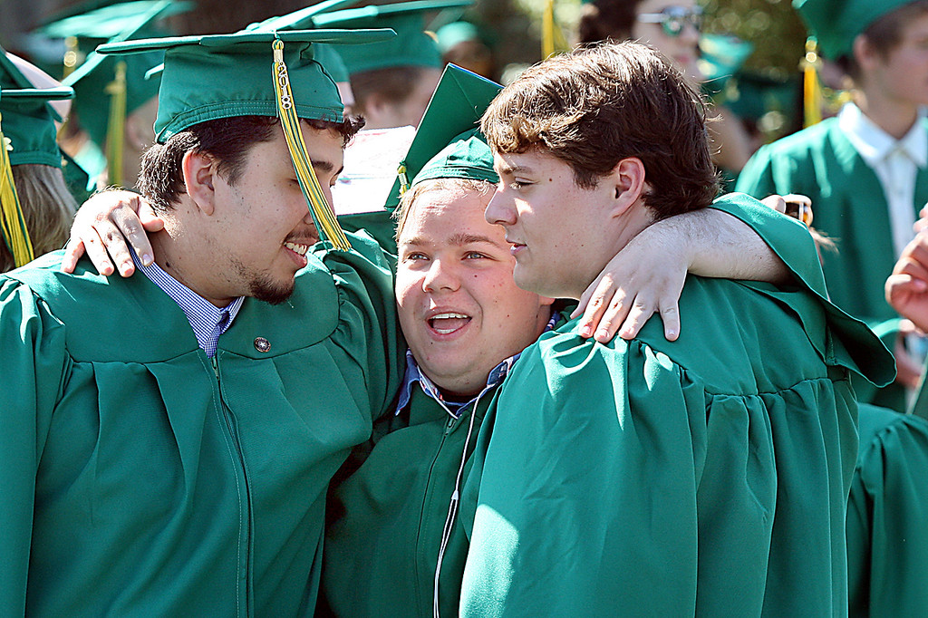 . Anthony Rivas, Brady Barnett, and Nicholas Bailey share a final moment as Harbor High seniors before marching to \'Pomp and Circumstance.\' Friday afternoon.  (Dan Coyro -- Santa Cruz Sentinel)