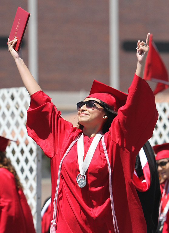 . Elizabeth Celine Sanchez raises her arms in the air during Lakewood High School\'s commencement Thursday at Veterans Memorial Stadium in Long Beach, CA Thursday, June 12, 2014. (Photo by Mark Dustin for the Press-Telegram)