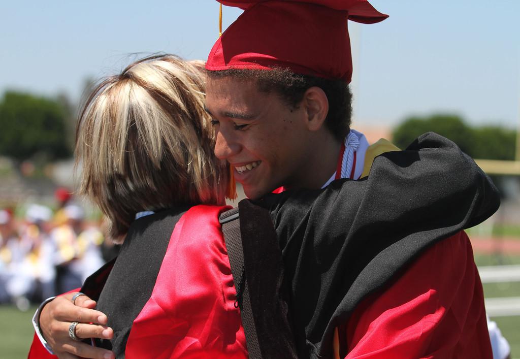 . Music teacher Stacy Burcham, left, hugs her student Charles Jacob Avington, right, during Lakewood High School\'s commencement Thursday at Veterans Memorial Stadium in Long Beach, CA Thursday, June 12, 2014. (Photo by Mark Dustin for the Press-Telegram)