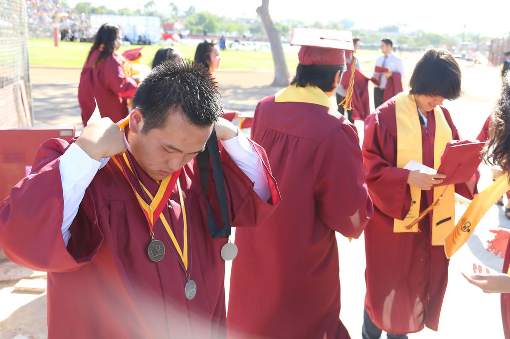 . Tsimaukua Xiong, left, gets ready along with his fellow classmates before Thursday evening\'s commencement at Stephens Field at Woodrow Wilson Classical High School in Long Beach, CA Thursday, June 12, 2014. (Photo by Mark Dustin for the Press-Telegram)