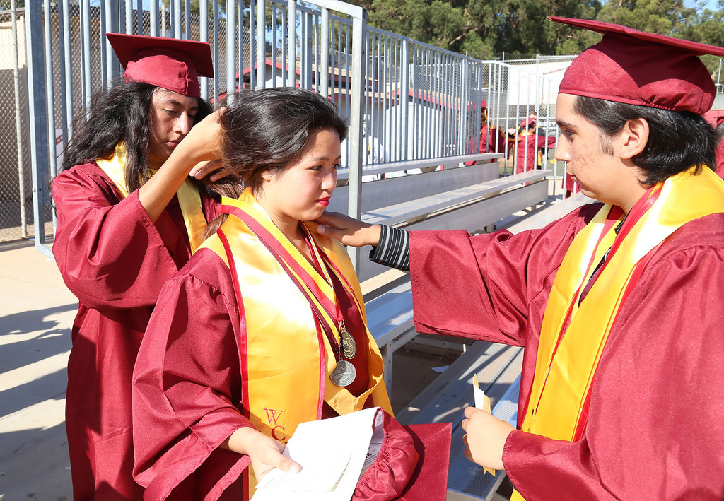 . Cristian Nava, left, and Armando Valencia, right, help Diana Preza, center, get ready for Thursday evening\'s commencement at Stephens Field at Woodrow Wilson Classical High School in Long Beach, CA Thursday, June 12, 2014. (Photo by Mark Dustin for the Press-Telegram)