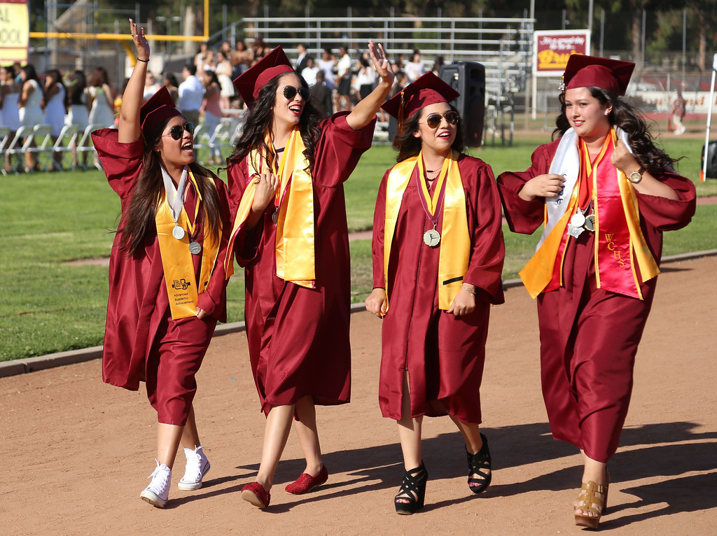 . Jocelyn Montiel, Conrada Ortiz, Lilibeth Medina, and Melissa Gonzalez walk on the track during the processional during Thursday evening\'s commencement at Stephens Field at Woodrow Wilson Classical High School in Long Beach, CA Thursday, June 12, 2014. (Photo by Mark Dustin for the Press-Telegram)