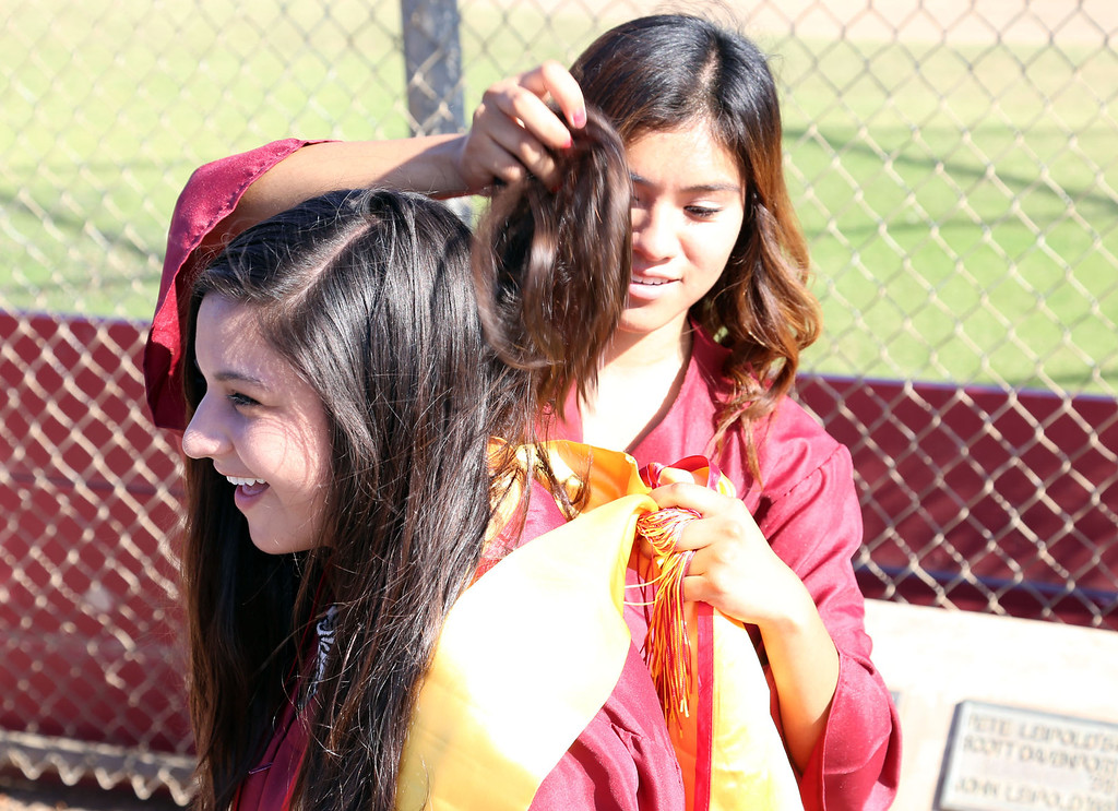 ". Isla Eustaquio, back, lifts Astrid ""Noodle\"" Aguirre\'s hair out of the way of her sash while getting ready for Thursday evening\'s commencement at Stephens Field at Woodrow Wilson Classical High School in Long Beach, CA Thursday, June 12, 2014. (Photo by Mark Dustin for the Press-Telegram)"