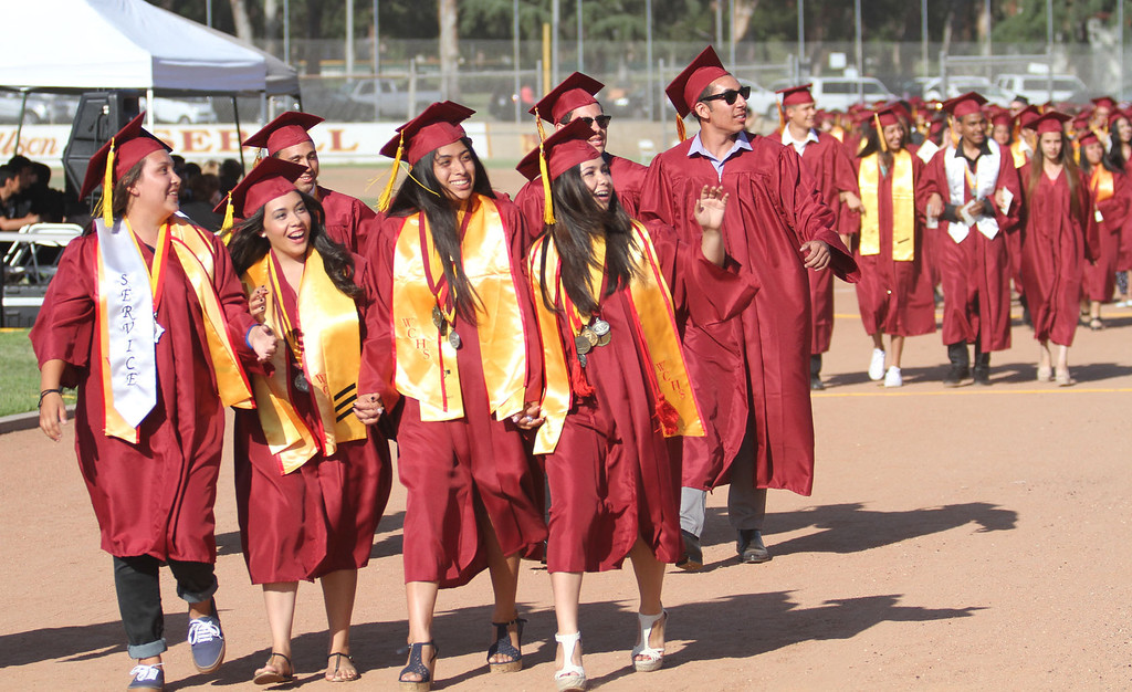 . Graduate candidates walk on the track during the processional during Thursday evening\'s commencement at Stephens Field at Woodrow Wilson Classical High School in Long Beach, CA Thursday, June 12, 2014. (Photo by Mark Dustin for the Press-Telegram)