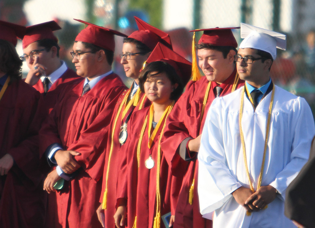 . Graduate candidates look on as the Downey High School Jazz Choir performs the National Anthem during Downey High School\'s 111th Commencement Ceremony Wednesday evening in Falcon Stadium at Cerritos College in Norwalk, CA Wednesday, June 18, 2014. (Photo by Mark Dustin for the Press-Telegram)