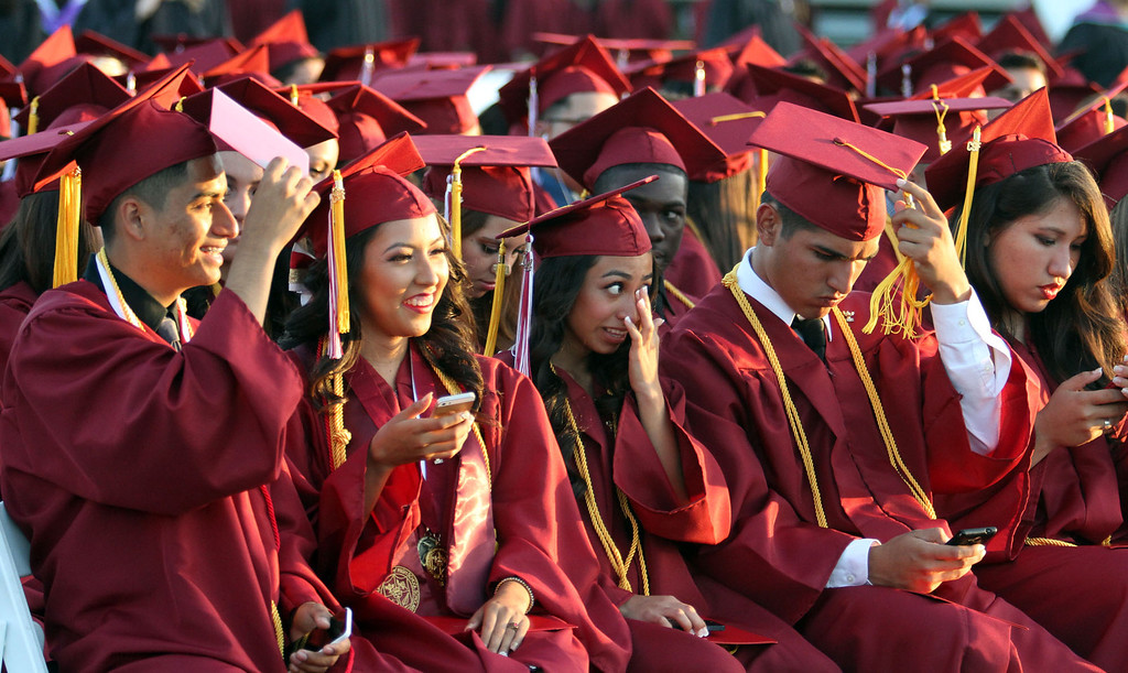 . Graduate candidates sit and wait during the Diploma Presentation portion of Downey High School\'s 111th Commencement Ceremony Wednesday evening in Falcon Stadium at Cerritos College in Norwalk, CA Wednesday, June 18, 2014. (Photo by Mark Dustin for the Press-Telegram)