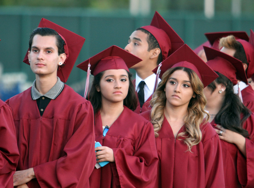 . Graduate candidates watch classmates receive their diploma holders while waiting in line during the Diploma Presentation during Downey High School\'s 111th Commencement Ceremony Wednesday evening in Falcon Stadium at Cerritos College in Norwalk, CA Wednesday, June 18, 2014. (Photo by Mark Dustin for the Press-Telegram)