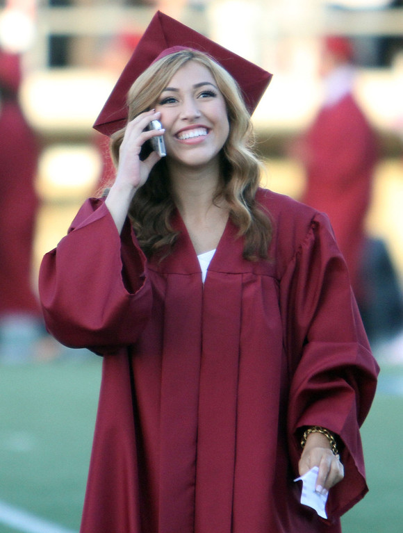 . Graduate candidate talks on her phone and looks in the stands during Downey High School\'s 111th Commencement Ceremony Wednesday evening in Falcon Stadium at Cerritos College in Norwalk, CA Wednesday, June 18, 2014. (Photo by Mark Dustin for the Press-Telegram)