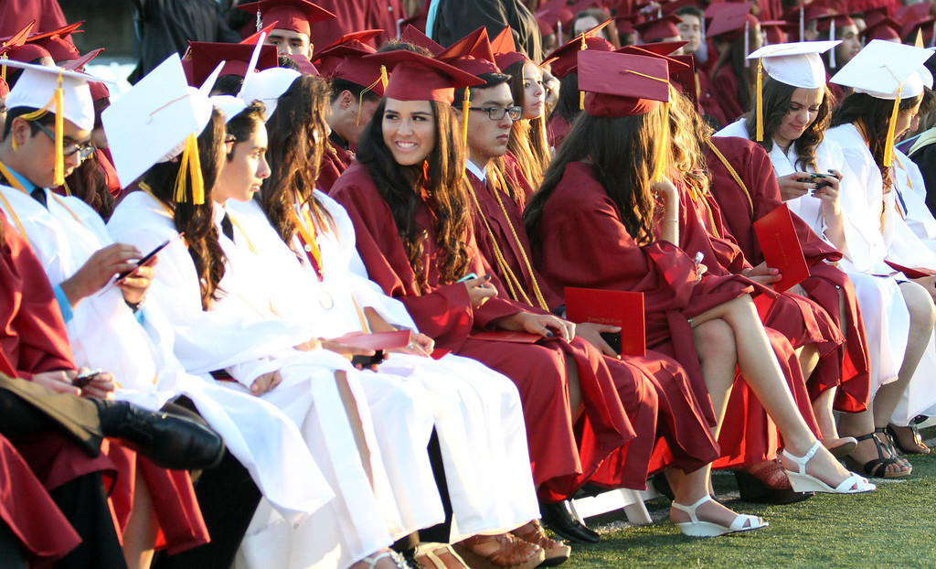 . Graduate candidates chat and play on their phones during the Diploma Presentation during Downey High School\'s 111th Commencement Ceremony Wednesday evening in Falcon Stadium at Cerritos College in Norwalk, CA Wednesday, June 18, 2014. (Photo by Mark Dustin for the Press-Telegram)