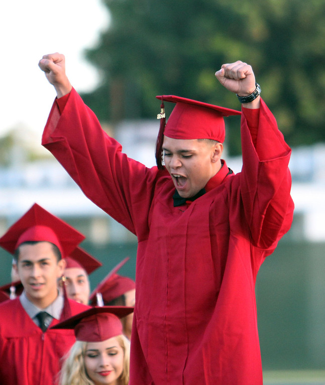 . Jonathan Ortega raises his arms in the air in triumph after being announced in the Diploma Presentation during Downey High School\'s 111th Commencement Ceremony Wednesday evening in Falcon Stadium at Cerritos College in Norwalk, CA Wednesday, June 18, 2014. (Photo by Mark Dustin for the Press-Telegram)