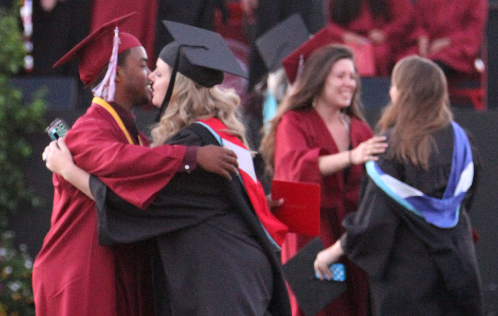 . Graduate candidates hug teachers after receiving their diploma holders during Downey High School\'s 111th Commencement Ceremony Wednesday evening in Falcon Stadium at Cerritos College in Norwalk, CA Wednesday, June 18, 2014. (Photo by Mark Dustin for the Press-Telegram)