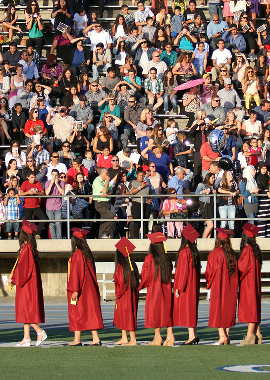 . Graduate candidates look up to the stands while waiting in line during the Diploma Presentation during Downey High School\'s 111th Commencement Ceremony Wednesday evening in Falcon Stadium at Cerritos College in Norwalk, CA Wednesday, June 18, 2014. (Photo by Mark Dustin for the Press-Telegram)