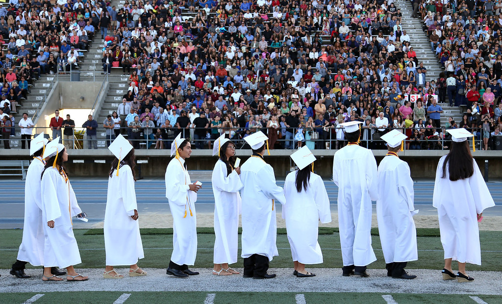 . Graduate candidates line up along the sideline while waiting their turn during the Diploma Presentation during Downey High School\'s 111th Commencement Ceremony Wednesday evening in Falcon Stadium at Cerritos College in Norwalk, CA Wednesday, June 18, 2014. (Photo by Mark Dustin for the Press-Telegram)
