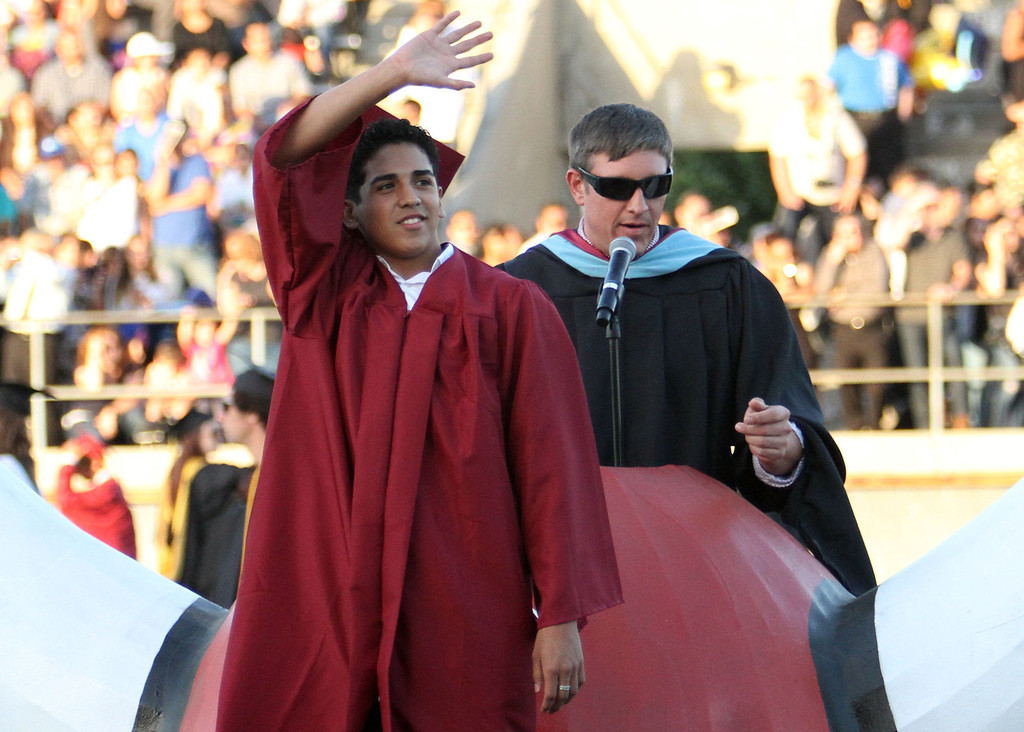 . Oscar Aguilar waves to the crowd after being announced to the crowd during Downey High School\'s 111th Commencement Ceremony Wednesday evening in Falcon Stadium at Cerritos College in Norwalk, CA Wednesday, June 18, 2014. (Photo by Mark Dustin for the Press-Telegram)