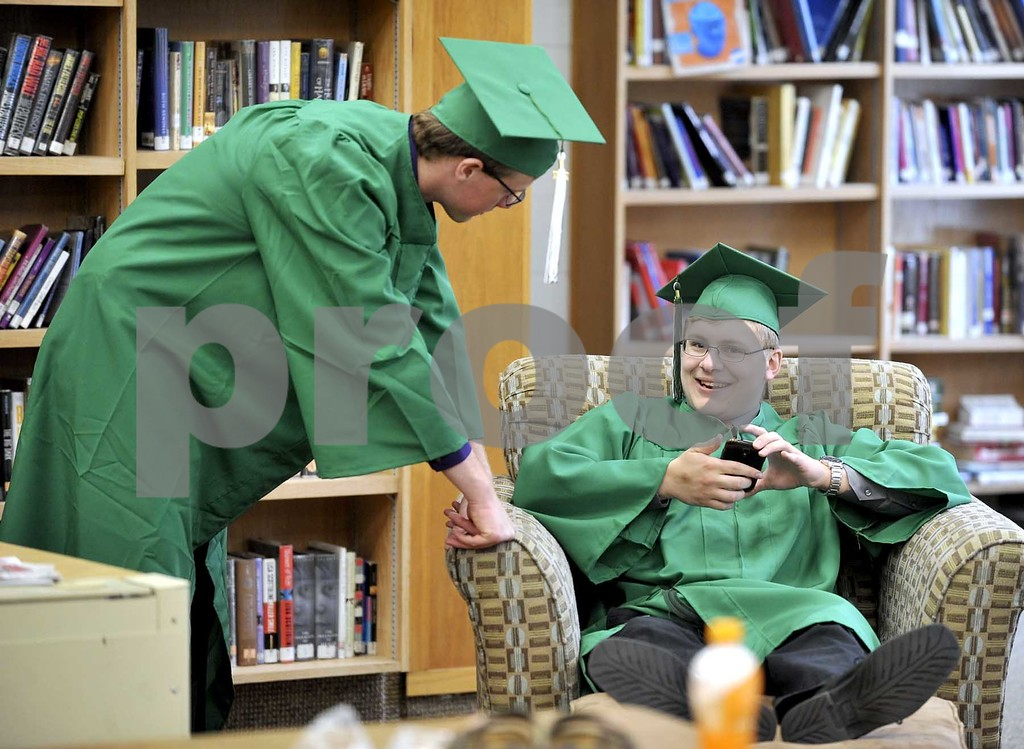 -Messenger photo by Hans Madsen<br /> <br /> Alex Sanck, right, is all smiles after a succesful upload to social media on his phone as his friend, Keaton Peart, left, looks on. The pair were waiting for commencement to start at St. Edmond Catholic School Sunday afternoon.