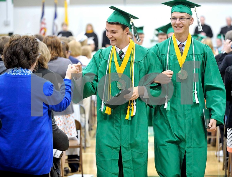 -Messenger photo by Hans Madsen<br /> <br /> Jake Heidenreich, at left, gives a fist pump to a member of the audience Sunday afternoon after getting his diploma during the St. Edmond Catholic School commencement. Trent Woodhouse, at right, did the same a few seconds before to a member of the audience on his side.