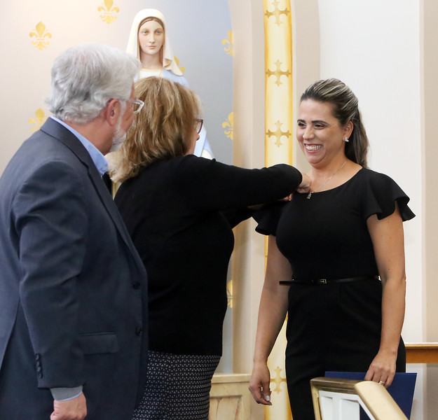Graduation for Certified Nursing Assistants training program, co-sponsored by Lowell Adult Ed, MCC, International Institute of New England, D'Youville, and Mass DESE. Cleide Oliveira of Billerica gets a pin from MCC course instructor Debbie Shaw. At left is MCC provost and VP Phil Sisson. (SUN Julia Malakie)