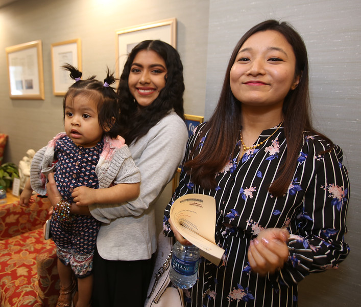 Graduation for Certified Nursing Assistants training program, co-sponsored by Lowell Adult Ed, MCC, International Institute of New England, D'Youville, and Mass DESE. From right, graduates Reema Shresthe of Boston and Anabel Peralta of Lowell, holding her daughter Leslie Garcia, 18 months. (SUN Julia Malakie)
