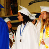 Debbie Blank | The Herald-Tribune<br /> Students rose in rows to stand near the stage's entrance ramp. As Student Council President Madeline Pierson read the first, middle and last names of 166 students, senior class representative Audrey Weigel assisted the superintendent as he presented the diplomas.