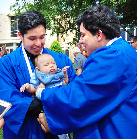 "Debbie Blank | The Herald-Tribune<br /> Three-month-old Weston Blanco came to see his cousins, Oscar Camarena (left) and Jilberto Davalos, graduate from high school. Camarena, bound for Ball State University to study marketing and advertising, observed, ""I feel really excited. I'm definitely going to miss this place and the memories I've made here."""