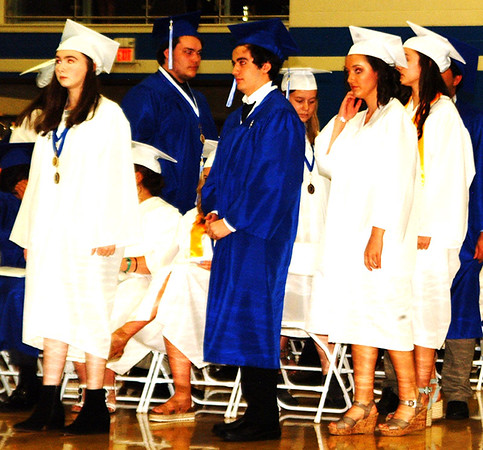 Debbie Blank | The Herald-Tribune<br /> As Student Council President Caroline Fitzpatrick read the names of each student, senior class representative Sophia Brown assisted the superintendent as he presented the diplomas to 184 Bulldogs. Here a group are approaching the stage.