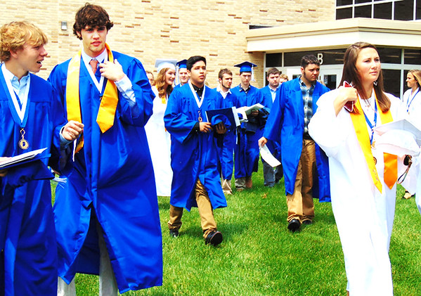 Debbie Blank | The Herald-Tribune<br /> The gym was sweltering, so it was good for the grads to get outside to greet loved ones.