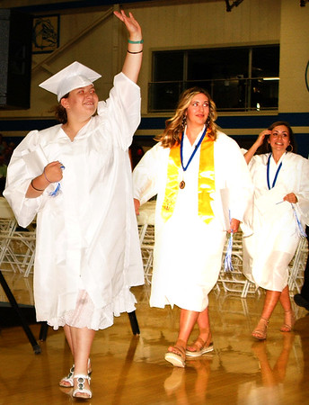 Debbie Blank | The Herald-Tribune<br /> Emily Addison waves triumphantly as she leaves the gym carrying her diploma. Following her are Lily Abplanalp and Caroline Fitzpatrick.