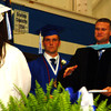 Debbie Blank | The Herald-Tribune<br /> SUPERINTENDENT Dr. Jim Roberts (from right), with the assistance of Studen Council President Graham Hunter, hands a diploma to one of 169 graduates.