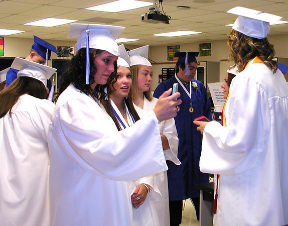 Debbie Blank | The Herald-Tribune<br /> BATEVILLE HIGH SCHOOL SENIORS killed time browsing through phone messages as they awaited the ceremony.