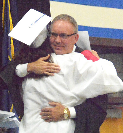Will Fehlinger | The Herald-Tribune<br /> Superintendent Paul Ketcham embraces his daughter, Madeline, after presenting her with her diploma.