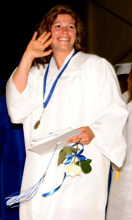 Debbie Blank | The Herald-Tribune<br /> This ecstatic graduate waves to fans as she leaves the gym.