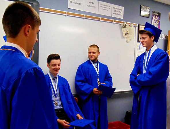 "Debbie Blank | The Herald-Tribune<br /> A group of friends kill time in a classroom before the 11 a.m. ceremony began. A sign above them urges, ""Work hard."""