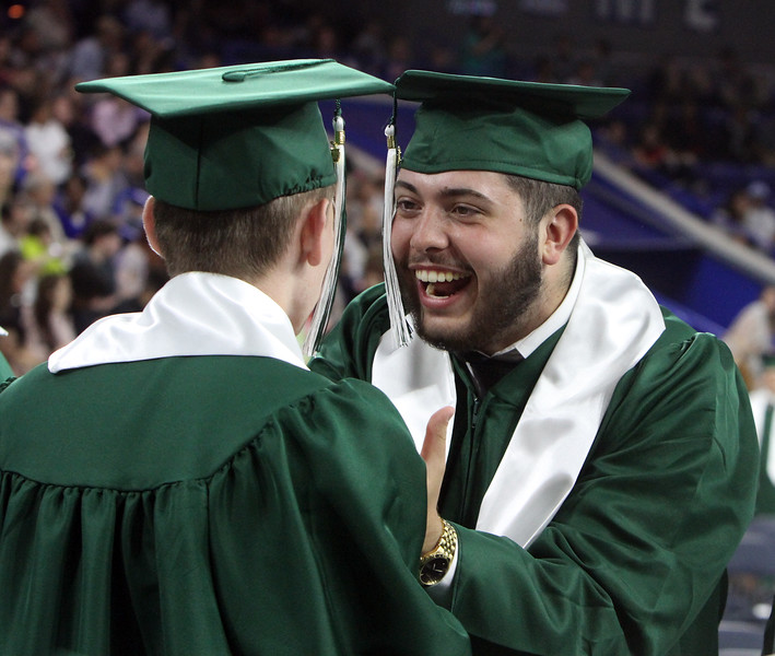 Matthew Milano, right, congratulates Ian Gibbons, who was on his way back to his seat, at Billerica High graduation. (SUN/Julia Malakie)
