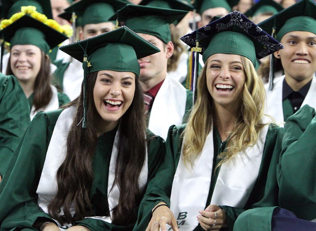 . Billerica High graduation. Christie Baglio, front left, and Jenna Balboni, right, laugh at class president Sean Stefaniak\'s speech. (SUN/Julia Malakie)