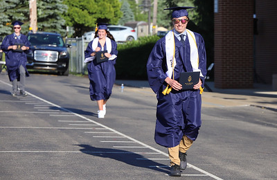 Zach Leachman walks through the parking lot of Mars High School during the school's graduation cermony Friday. With social distancing guidlines, the school district held graduation in the high school parking lot with families parked in every other spot. Students recieved their diploma, posed for pictures and then walked through the parking lot to cheers and congratulations. Seb Foltz/Butler Eagle 06/12/20