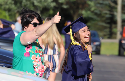 Kiara Khemani and her mom Deanna cheer on graduates walking at Mars Area School District Graduation Friday.  With social distancing guidlines, the school district held graduation in the high school parking lot with families parked in every other spot. Students recieved their diploma, posed for pictures and then walked through the parking lot to cheers and congratulations. Seb Foltz/Butler Eagle 06/12/20