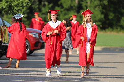 Bryce Kopchak and Carlie Kreutzer walk through the North Catholic High School parking lot during graduation ceremonies Friday. Seb Foltz/Butler Eagle 0724/20