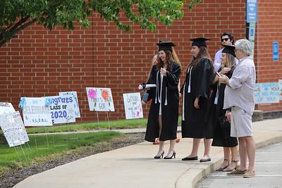 Seneca Valley seniors look at signs lining the drive through campus to NexTier Stadium following graduation Friday. Seb Foltz/Butler Eagle