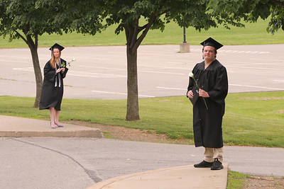 Maintaining appropriate social distance, Michael Van Pelt (right) and Morgan Wehr wait to be picked up by their families after walking at Seneca Valley's graduation ceremony Friday. Families of graduates dropped off their kids watched them walk and then picked them up in order to minimize social contact. Seb Foltz/Butler Eagle
